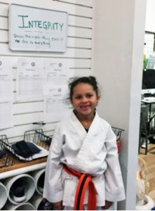 child in Taekwondo clothing with poster celebrating integrity