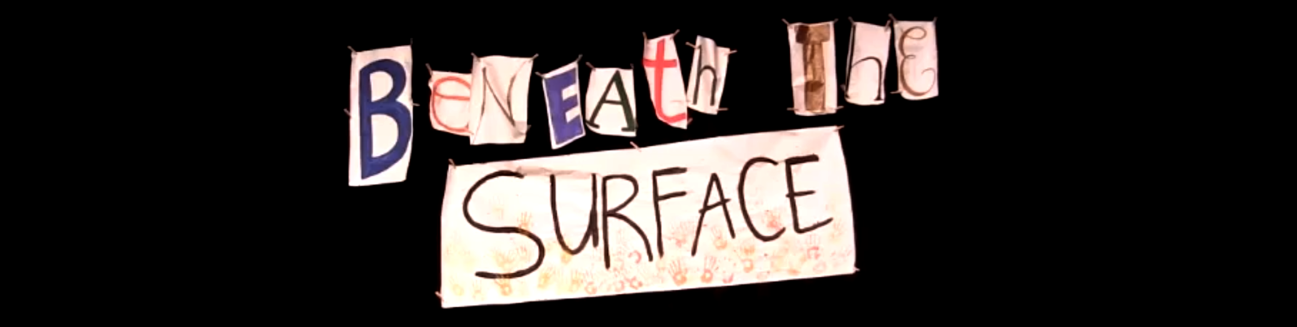 Beneath the Surface banner with letters cut out on a black curtain